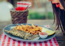 吃新鲜的鲜美鱼用炸薯条的少妇 库存图片