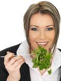 吃新鲜的绿色叶子沙拉的年轻女商人 免版税图库摄影