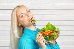 吃新鲜蔬菜沙拉的女孩 免版税库存图片