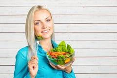吃新鲜蔬菜沙拉的女孩 免版税库存照片