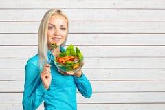 吃新鲜蔬菜沙拉的女孩 免版税图库摄影