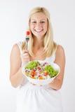吃新鲜蔬菜的愉快的少妇 免版税库存照片