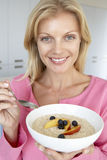 吃新鲜水果中间粥妇女的成人 免版税库存照片