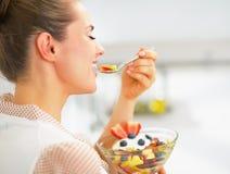 吃新鲜水果沙拉的愉快的年轻主妇在厨房里 免版税图库摄影