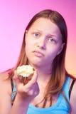 吃无味的苹果的不快乐的青少年的女孩 免版税库存图片