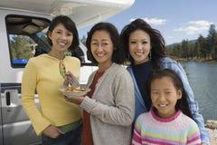 吃早餐在RV外面的三代妇女在湖 免版税库存照片