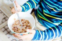 吃早餐或午餐的孩子男孩的手特写镜头自创谷物 免版税库存图片