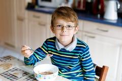 吃早餐或午餐的愉快的矮小的白肤金发的孩子男孩谷物 健康吃子项的 免版税库存图片