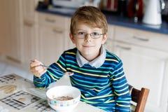 吃早餐或午餐的愉快的矮小的白肤金发的孩子男孩谷物 健康吃子项的 免版税图库摄影