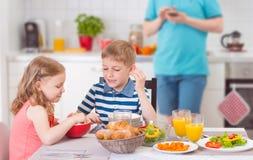 吃早餐的两个愉快的孩子在父亲工作期间 免版税库存照片