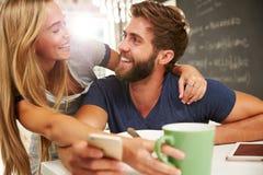 吃早餐的夫妇使用数字式片剂和电话 库存照片