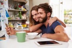 吃早餐的夫妇使用数字式片剂和电话 免版税库存照片