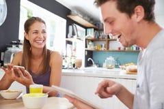 吃早餐的夫妇使用数字式片剂和电话 图库摄影