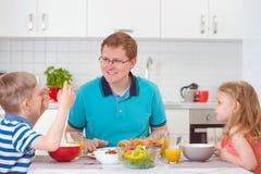 吃早餐的微笑的家庭在厨房里 库存图片