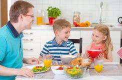 吃早餐的微笑的家庭在厨房里 免版税图库摄影