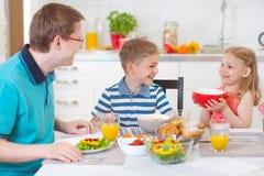 吃早餐的微笑的家庭在厨房里 库存照片