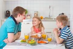 吃早餐的微笑的家庭在厨房里 免版税库存照片
