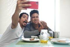 吃早餐的快乐夫妇采取与电话的Selfie 免版税库存图片