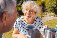 吃早餐的愉快的年长夫妇在他们的庭院里户外 免版税库存图片