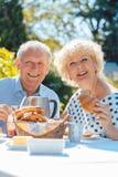 吃早餐的愉快的年长夫妇在他们的庭院里户外 免版税库存照片