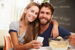 吃早餐的年轻夫妇,使用手机 免版税库存照片