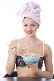 吃早餐谷物的少妇穿女用贴身内衣裤 免版税库存照片