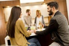 吃晚餐和喝酒的小组青年人在现代 免版税库存照片