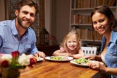 吃晚餐的家庭在一张餐桌上,看照相机 免版税库存照片