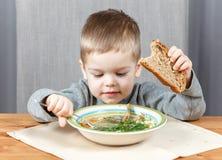 吃晚餐的小男孩汤 免版税库存图片