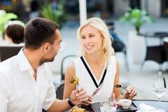 吃晚餐的愉快的夫妇在餐馆大阳台 免版税库存图片