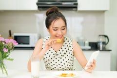 吃曲奇饼和微笑,使用智能手机的年轻微笑的妇女 图库摄影
