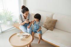 吃曲奇饼和饮用奶与她的母亲的可爱的女孩 免版税库存图片