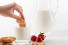 吃曲奇饼用新鲜的牛奶和草莓的人 库存照片