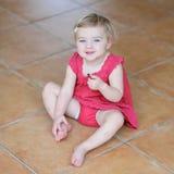 吃曲奇饼的小女孩坐地板 免版税图库摄影