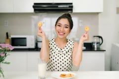 吃曲奇饼的早晨早餐愉快的女孩坐在厨房里 免版税库存图片