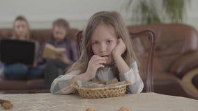 吃曲奇饼的画象可爱的小女孩坐在桌上和看照相机 被弄脏的图年轻 股票视频