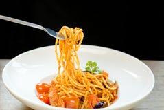 吃有叉子的意大利食物妇女意粉在白色板材 免版税库存照片