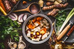 吃有机农厂的菜烹调和 烹调有切成小方块的五颜六色的根菜类的罐在土气厨房用桌背景wi 免版税库存照片