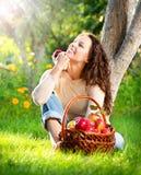 吃有机Apple的女孩在果树园 免版税库存照片