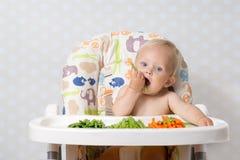 吃未加工的食物的女婴 免版税图库摄影