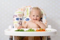 吃未加工的食物的女婴 免版税库存图片