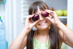 吃李子的愉快的女孩站立近的冰箱 免版税库存照片