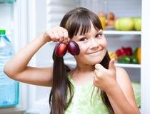 吃李子的愉快的女孩站立近的冰箱 库存图片