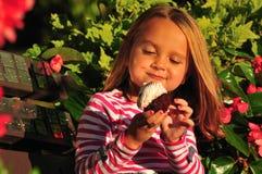 吃杯形蛋糕的可爱的女孩 免版税库存图片