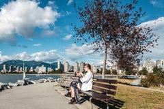 吃杯形蛋糕的女孩在基斯兰奴海滩在温哥华,加拿大 免版税库存图片