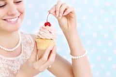 吃杯形蛋糕的妇女 免版税库存照片