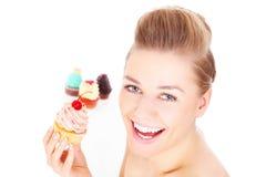 吃杯形蛋糕的愉快的妇女 免版税库存图片