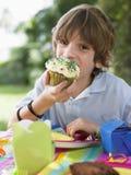 吃杯形蛋糕的年轻男孩在生日聚会 库存图片