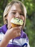 吃杯形蛋糕的年轻男孩在生日聚会 免版税图库摄影