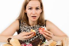 吃杯形蛋糕高兴地的少妇在饮食以后